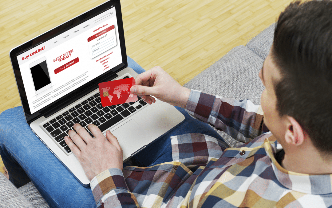 Man sitting at laptop holding a credit card